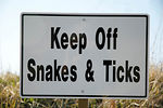 Stock photograph of humorous sign at a park that says to keep off snakes and ticks